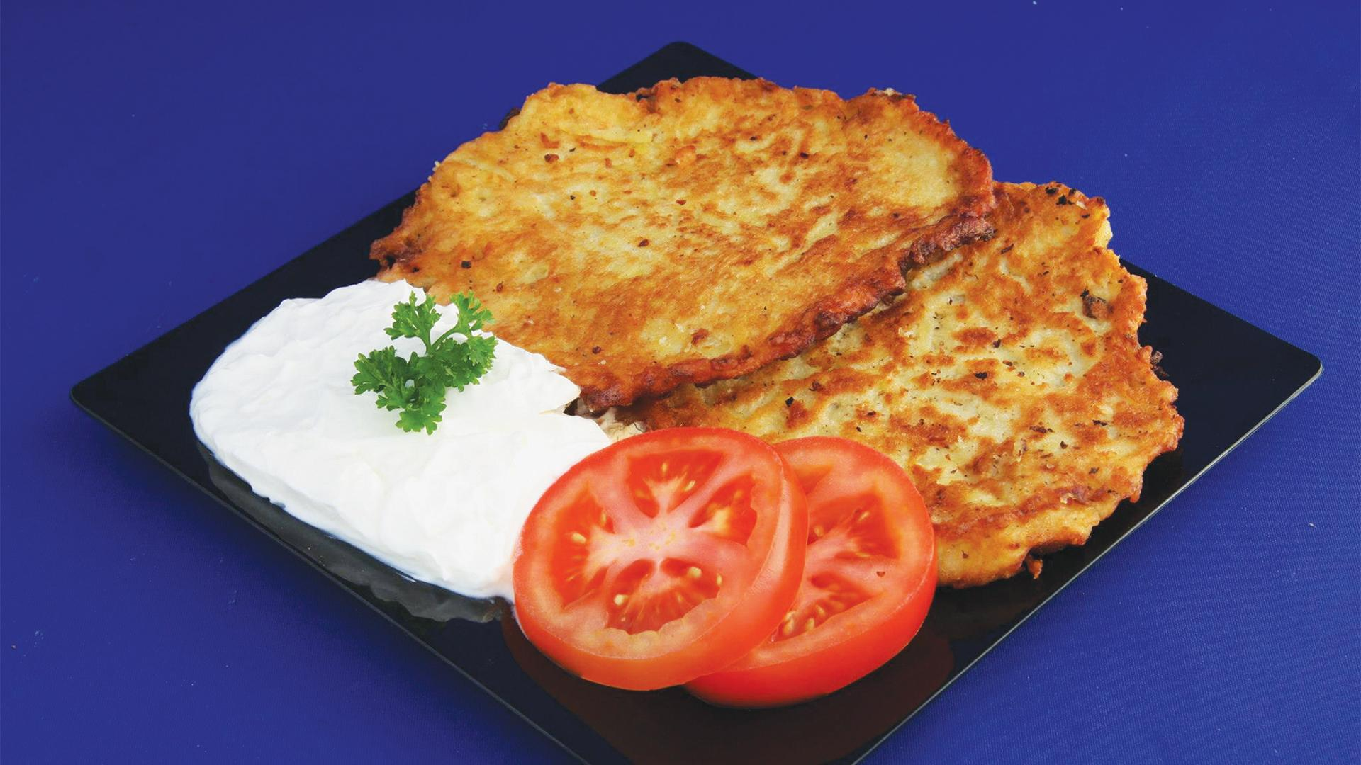 Toronto's best latkes | A plate of latkes with sour cream and tomatoes from Daiter's