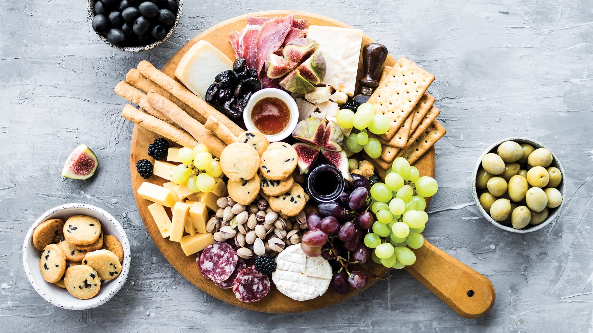 How to make the perfect holiday charcuterie board   Flat lay of charcuterie board with meat, cheese and garnishes