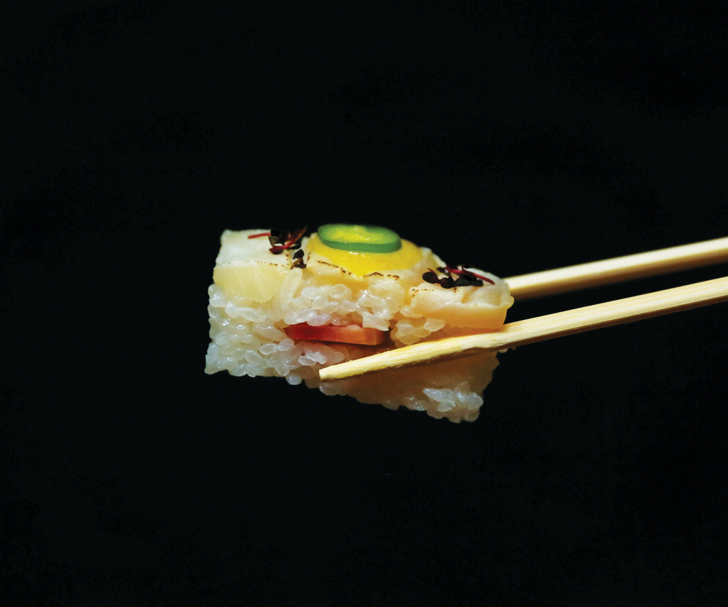 The different sushi types and how to eat them    Chopsticks hold a piece of yellowtail oshi at Minami Toronto
