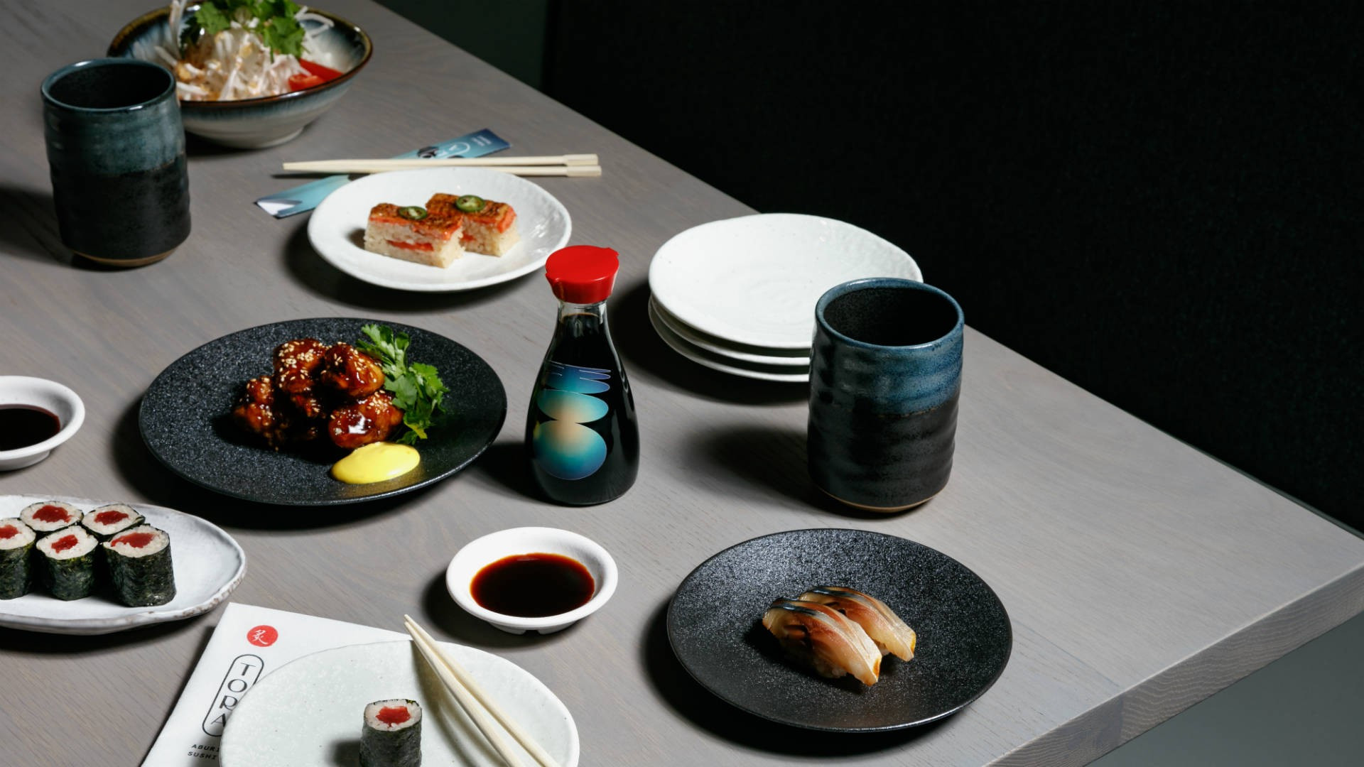 The best restaurants offering delivery and takeout in Toronto: table spread of sushi and Japanese fare at TORA