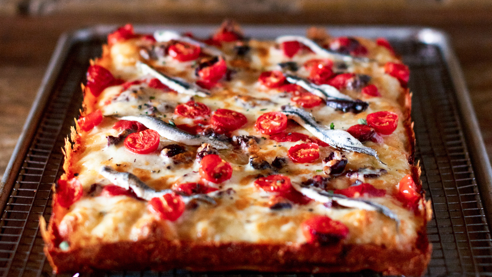 The best new restaurants in Toronto | Mediterranean Detroit-style pan pizza with boquerones, olives, tomatoes, cheese & tomato sauce at Gianna's Patties and Pies