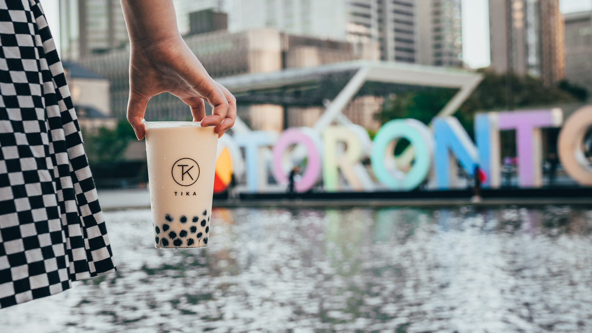 The best bubble tea in Toronto | a milk tea from Tika in front of the Toronto sign at Nathan Phillips Square