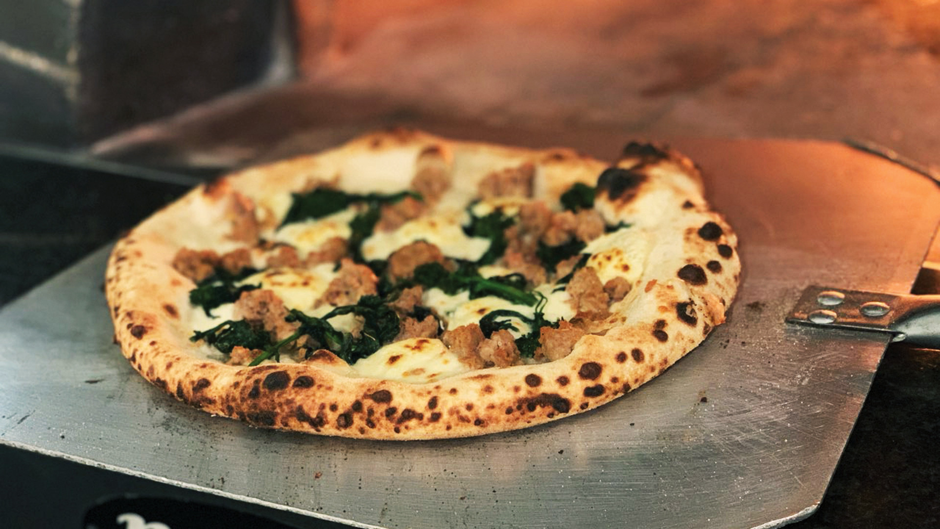 A pizza coming out of the authentic wood burning oven at La Fontana, one of the best Elora restaurants