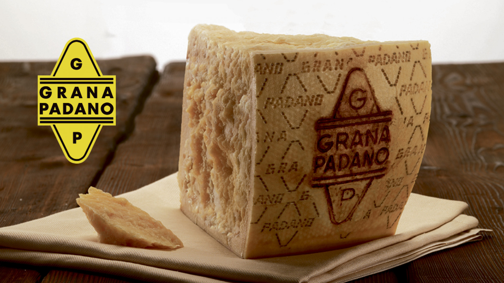 Grana Padano cheese on a rustic wood table