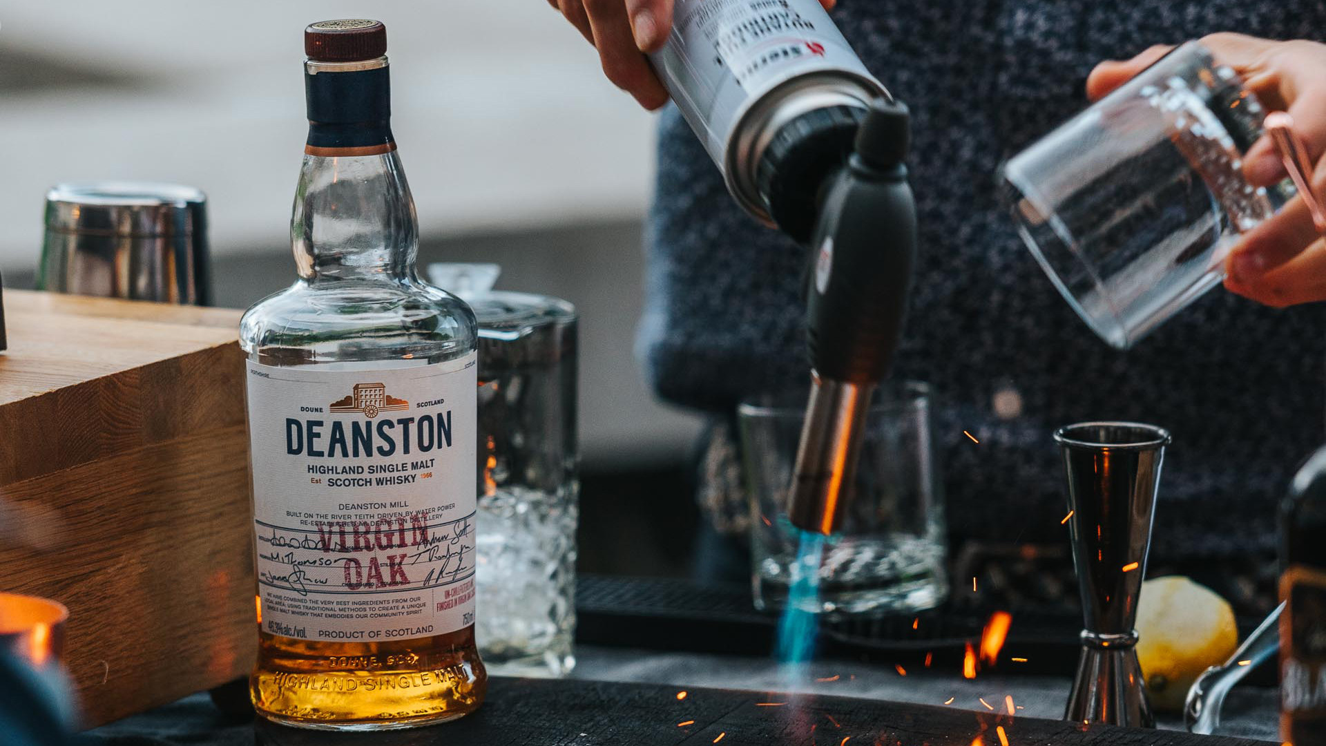 Deanston smoked old fashioned recipe | a bartender using a blow torch on a Spirits with Smoke cocktail smoking board