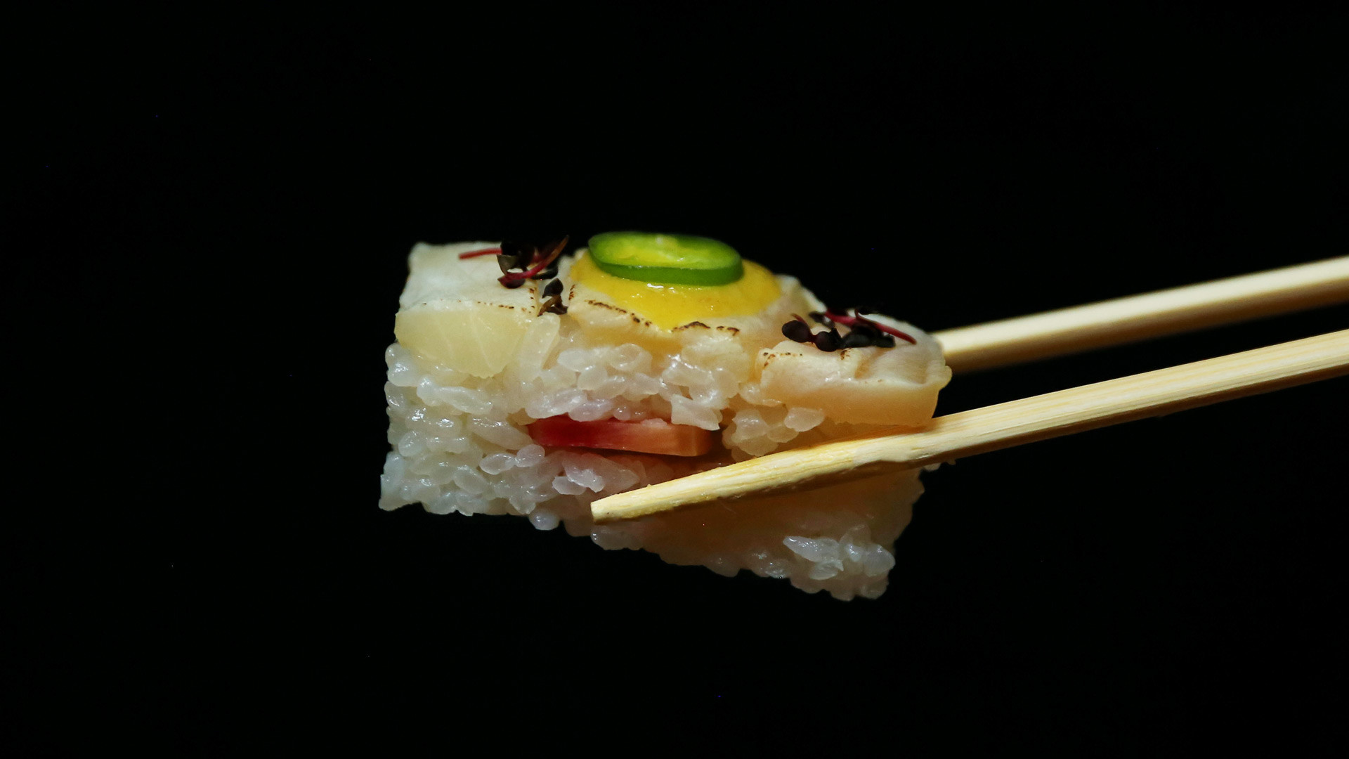 Sushi types and how to eat sushi | Chopsticks hold a piece of yellowtail oshi at Minami Toronto