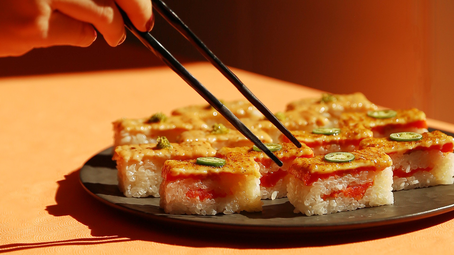 Sushi types and how to eat sushi | Chopsticks reach for a platter of salmon oshi at Minami Toronto