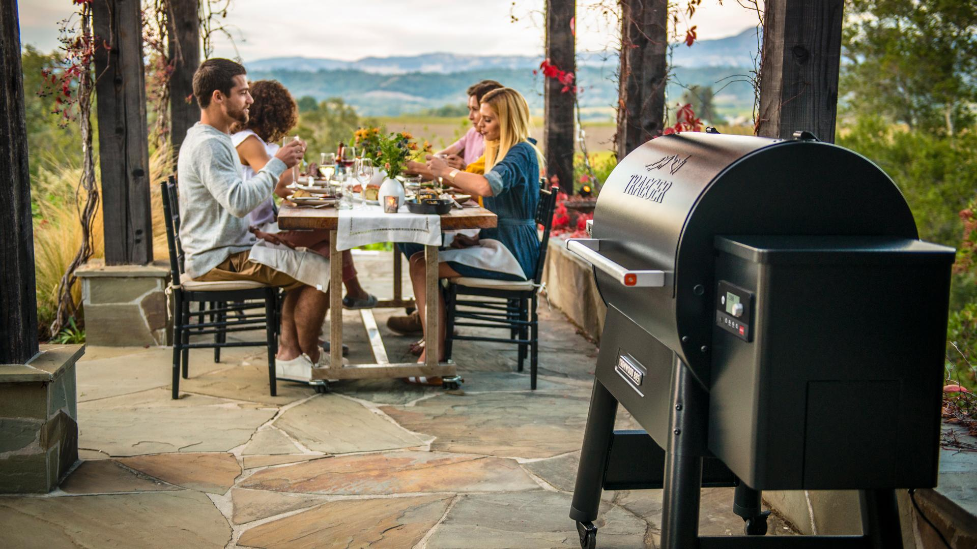 A group of people dine next to a Traeger grill