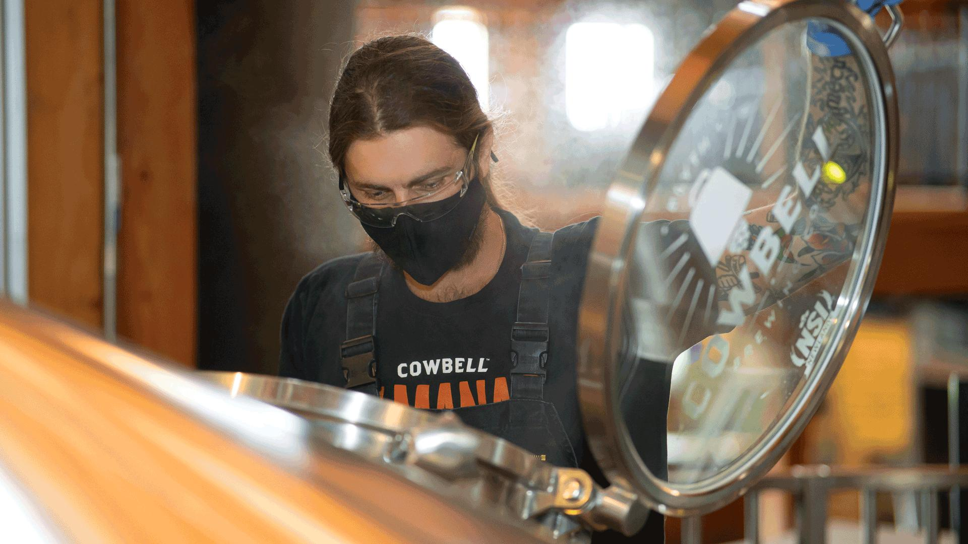 What is craft beer? An essential guide to Ontario craft beer | A brewer making craft beer at Cowbell Brewing Co.