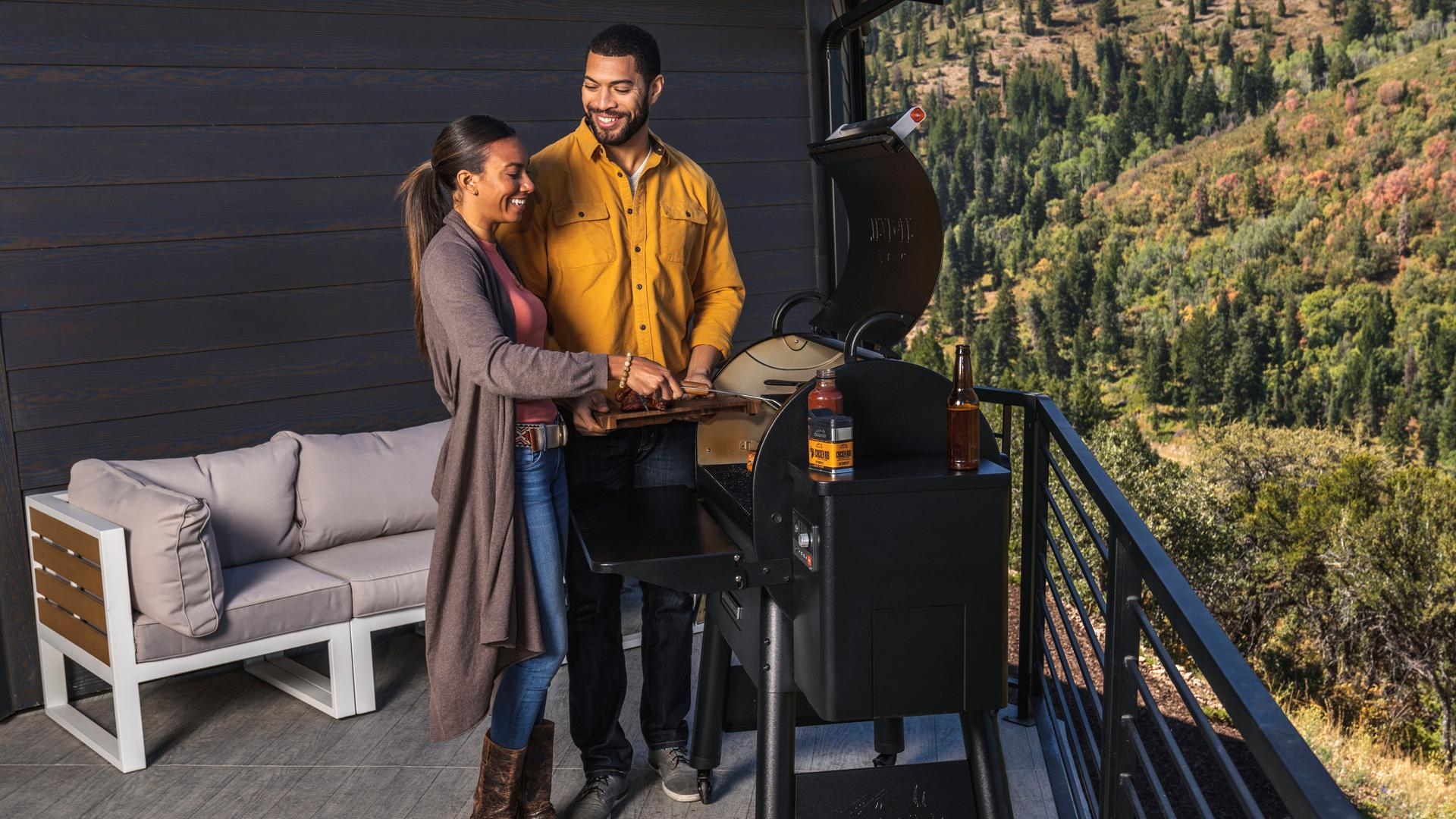 Win a Traeger Pro 575 Grill | A young couple cooks on a Traeger Grill