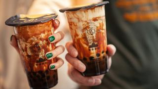 The best bubble tea in Toronto | two people holding brown sugar milk teas from Tiger Sugar