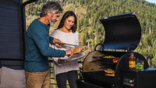 A couple cooks salmon on a Traeger grill