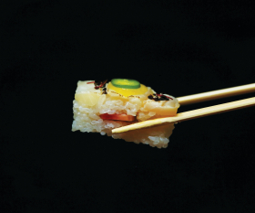 The different sushi types and how to eat them |  Chopsticks hold a piece of yellowtail oshi at Minami Toronto