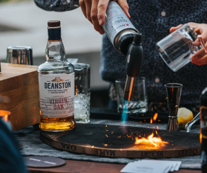 Deanston smoked old fashioned recipe | a bartender using a blow torch on a cocktail smoking board from Spirits with Smoke
