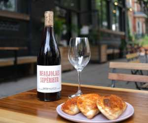 Somm wine app Grand Cru membership | A glass of wine and pastries on the patio